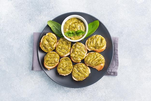 ペストソース、新鮮なバジルの葉、ニンニクのサンドイッチ。ヘルシーで美味しいおやつコピースペース