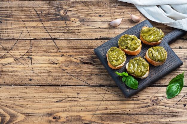ペストソース、新鮮なバジルの葉、ニンニクのサンドイッチ。ヘルシーなおやつ。木製の素朴な背景。コピースペース