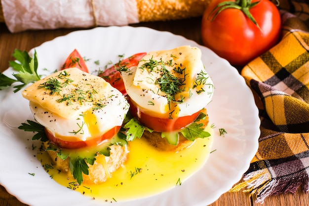 Sandwiches with poached egg, tomato, parsley and cheese