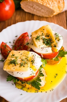 Sandwiches with poached egg, tomato, parsley and cheese.