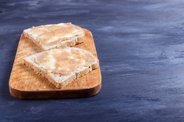 Sandwiches with pollock roe on a wooden kitchen board against black background