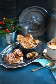 Sandwiches with prosciutto and soup in a mug on a gray surface