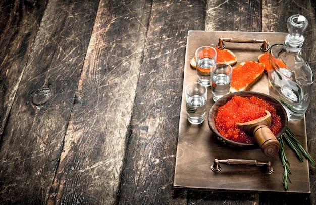빨간 캐 비어와 보드카 쟁반에 샌드위치. 나무 배경.
