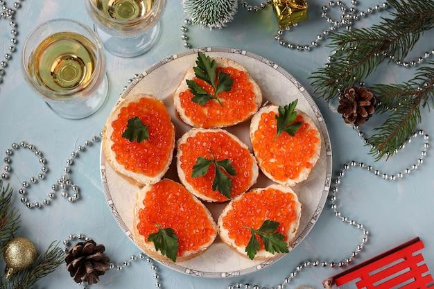 빨간 캐비어가 든 샌드위치는 연한 파란색 배경에 접시에 있습니다.