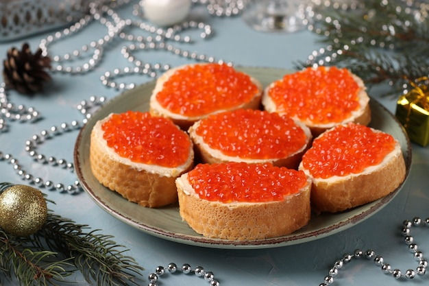 Sandwiches with red caviar are located on a plate against a light blue background. festive snack. closeup. horizontal orientation.