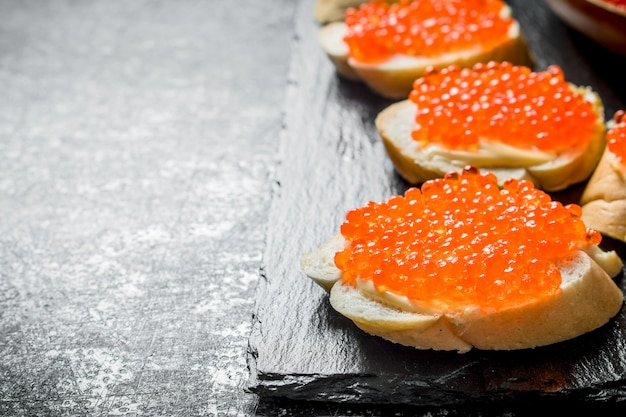 Sandwiches with red caviar. on black rustic background