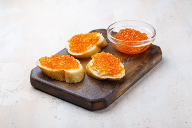Sandwiches with red caviar and butter in plate on wooden table. top view