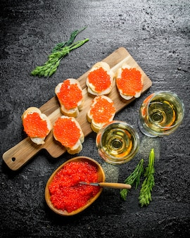 Sandwiches with red caviar on a cutting board and white wine in glasses. on black rustic surface