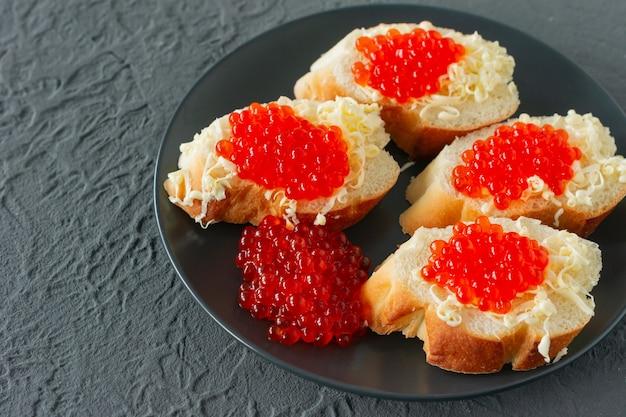 콘크리트 배경에 검정 접시에 빨간 캐비어, 레몬, 파슬리를 넣은 샌드위치. 해물.