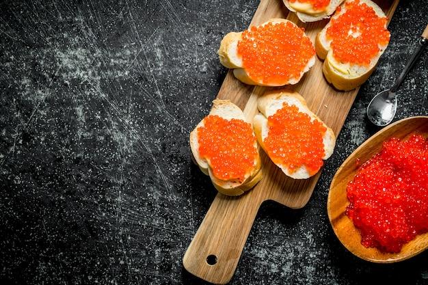 Бутерброды с красной икрой на деревянной разделочной доске. на черном деревенском фоне
