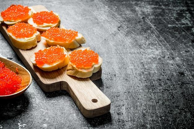 木製のまな板に赤キャビアのサンドイッチ。黒の素朴なテーブルの上
