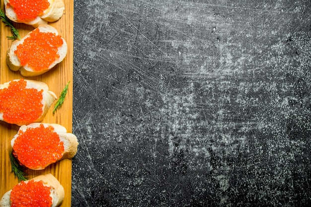 Sandwiches with red caviar on a wooden stand. on black rustic surface