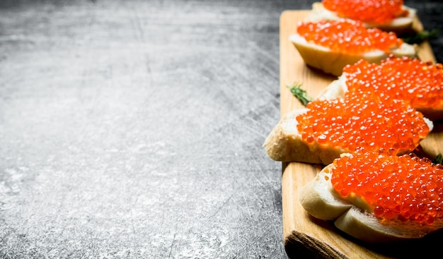 Sandwiches with red caviar on a wooden stand. on black rustic table