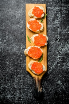 Sandwiches with red caviar on a wooden stand. on black rustic