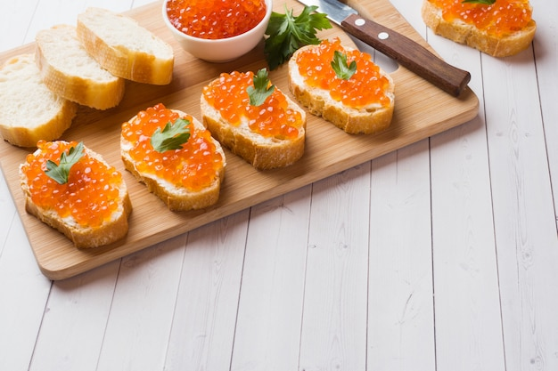 Sandwiches with red salmon caviar on a wooden board