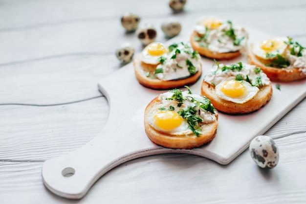 テーブルの上のホワイトボードに緑とリコッタチーズとウズラの卵のサンドイッチ