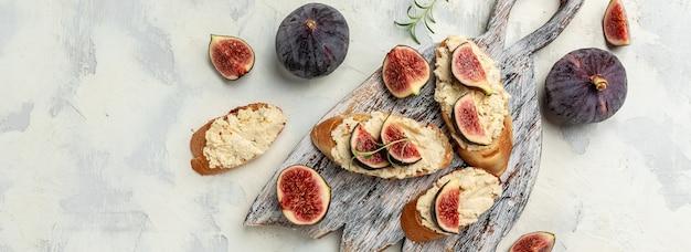 Бутерброды с сыром рикотта, инжиром, вкусная закуска, идеальный аперитив. вид сверху