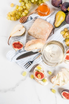Sandwiches with ricotta or cream cheese, ciabatta, fresh figs, pears, grape, walnuts and honey on white marble table table, with wine glass copyspace top view