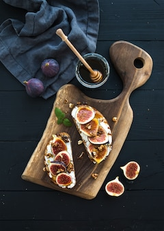 Sandwiches with ricotta, fresh figs, walnuts and honey on rustic wooden board