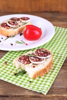 サラミ プレートと木製のテーブルのナプキンのサンドイッチ