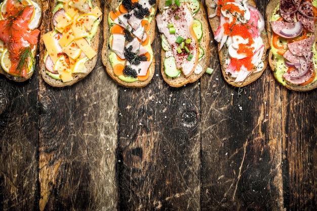 木製のテーブルにサーモン、チーズ、マッシュルーム、新鮮な野菜のサンドイッチ。