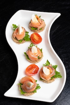 Бутерброды с лососем, вяленой брезаолой, раками, помидорами, перепелиными яйцами и сметаной. японская еда