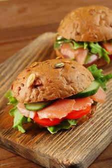 まな板、木の表面に鮭のサンドイッチ