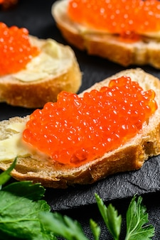 Sandwiches with salmon red caviar. black surface. top view