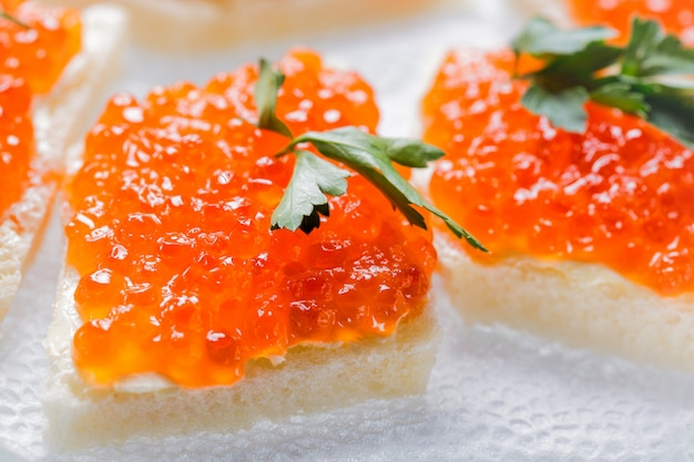 Sandwiches with salmon red caviar and herbs on white napkin