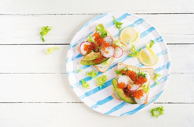 Бутерброды с лососевой красной икрой с нарезанным авокадо и редисом. сэндвич на обед. премиальная еда. накладные, вид сверху, плоская планировка