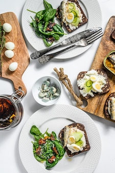Sandwiches with sardines, eggs, cucumber and cream cheese on white table