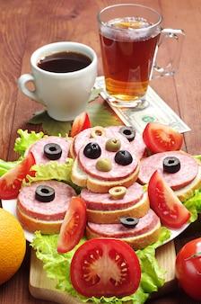 木製のテーブルにソーセージ、コーヒー、紅茶、1ドルのサンドイッチ