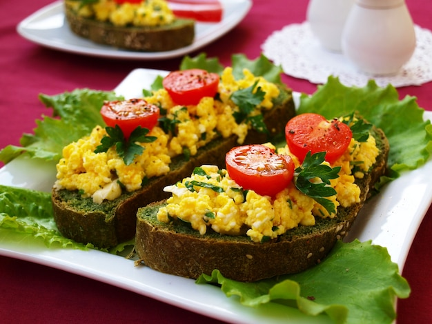 Sandwiches with scrambled eggs and cherry tomatoes on homemade bread with nettles