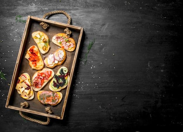 신선한 빵에 해산물, 고기 및 야채 샌드위치. 검은 칠판에.