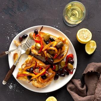 Бутерброды с дымом перцем, оливками и чесноком на светлом фоне, вид сверху. плоская планировка