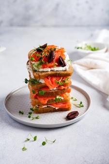 회색 세라믹 접시에 훈제 핑크 연어 올리브, 칼라마타, 마이크로그린, 크림 치즈를 넣은 샌드위치와 트렌디한 콘크리트 배경. 스칸디나비아 전통 토스트. 평면도