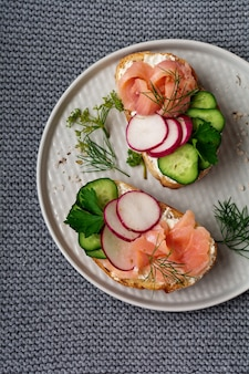 회색 세라믹 플레이트 및 섬유 표면에 훈제 핑크 연어, 무, 오이 및 크림 치즈 샌드위치