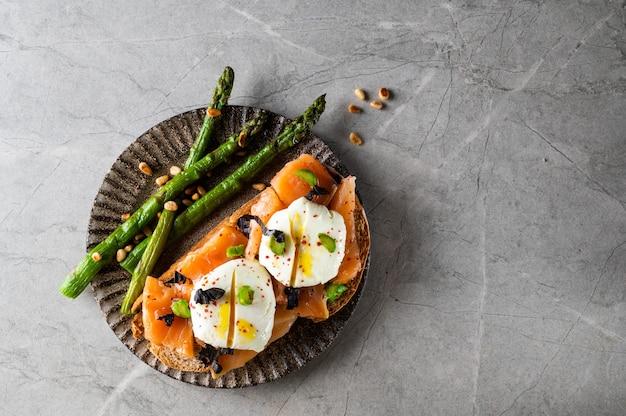 Бутерброды с копченым лососем и спаржей на светлом фоне камня, вид сверху.