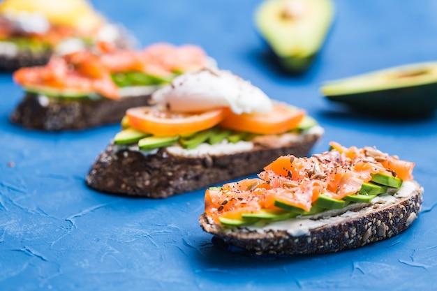 훈제 연어와 파란색 배경에 아보카도와 샌드위치. 건강한 영양에 대한 개념.
