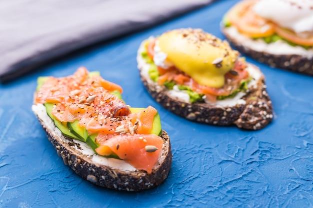 훈제 연어, 계란, 소스와 파란색 배경에 아보카도와 샌드위치. 아침의 개념과