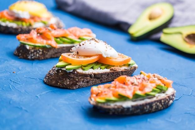 Бутерброды с копченым лососем, яйцами, соусом и авокадо на синем фоне. концепция завтрака и