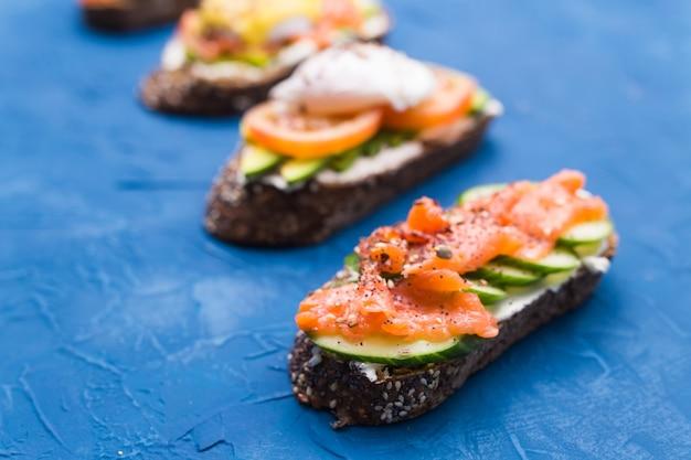 파란색 표면에 훈제 연어, 계란, 소스 및 아보카도와 샌드위치. 아침 식사와 건강한 영양의 개념.