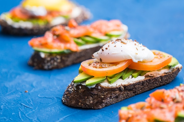 파란색 표면에 훈제 연어, 계란, 소스 및 아보카도와 샌드위치. 아침의 개념과