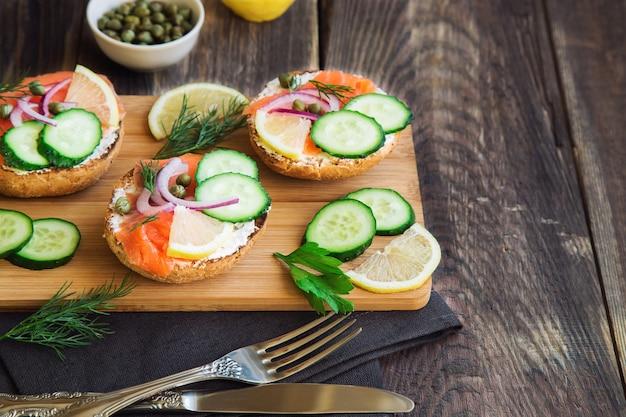 Бутерброды с копченым лососем, красным луком, каперсами, огурцом и лимоном на деревенском дереве.