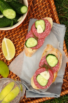 Sandwiches with smoked sausage and homemade fresh salted cucumbers in the bowl