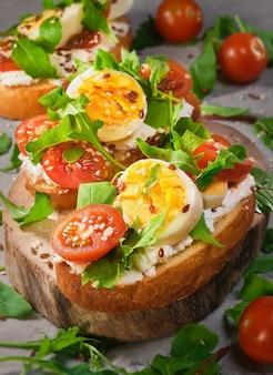 На деревенскую деревянную доску кладут бутерброды с мягким творогом или сыром, помидорами, рукколой и яйцом, посыпанные кунжутом. здоровая пища, тост брускетта, выборочный фокус крупным планом