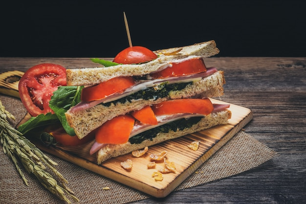 Sandwiches with spinach and tomatoes have cream sauce on the wood floor that looks inviting.