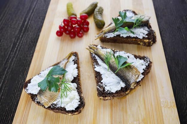 木の板にスプラットとガマズミ属の果実のサンドイッチ