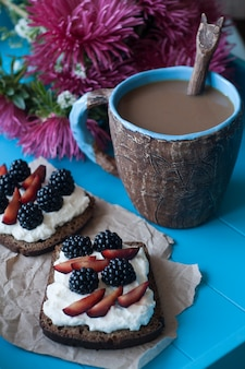 Sandwiches with sweet cheese and berries, a cup of coffee and a bouquet of asters in blue wooden surface