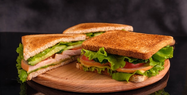 Sandwiches with tomatoes, cucumbers, ham and cheese